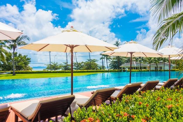 Guarda-chuva e cadeira em volta da piscina Foto gratuita
