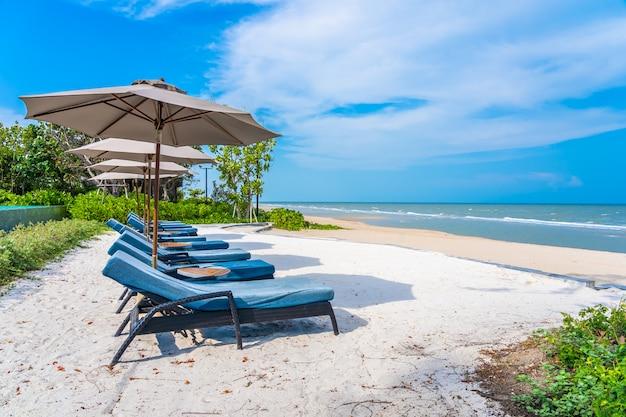 Guarda-chuva e cadeira na praia mar oceano com céu azul e nuvem branca Foto gratuita