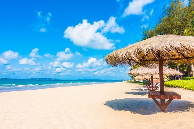 Guarda-chuva e cadeira na praia Foto gratuita