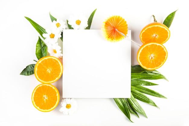 Guarda-chuva e folha de papel perto de laranjas e flores Foto gratuita