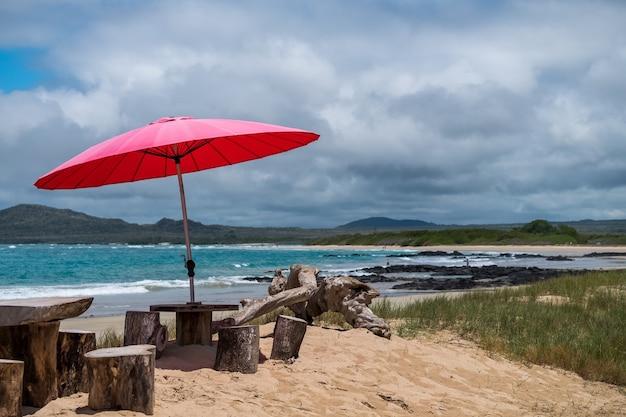 Guarda-chuva vermelho fornecendo sombra para as pessoas na praia nas ilhas galápagos, equador Foto gratuita