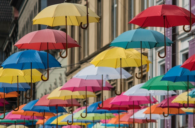 Guarda-chuvas coloridos pendurar no fundo da cidade velha em lviv Foto Premium