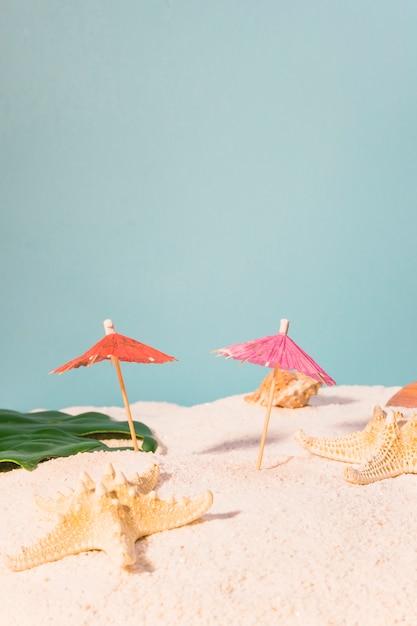 Guarda-chuvas de cocktail e estrela do mar na praia Foto gratuita