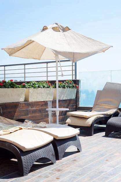 Guarda-sóis de cor bege e espreguiçadeiras com vista para o mar. Foto Premium