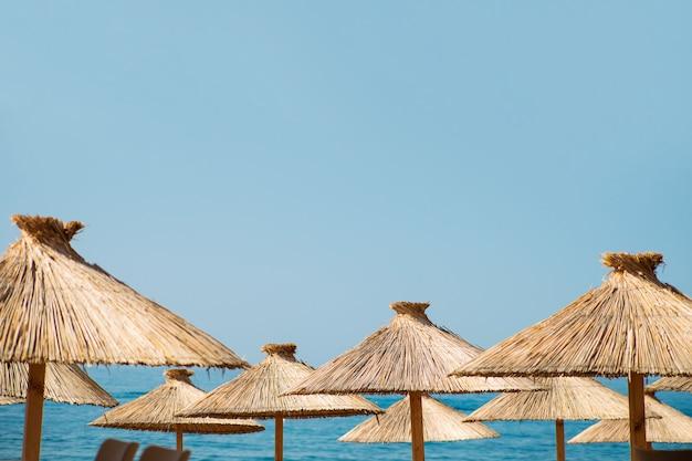 Guarda-sóis de palha em um fundo de céu azul e mar com um espaço de cópia Foto Premium