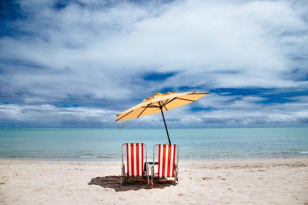 Guarda-sol de praia e cadeiras de praia vermelhas em uma praia Foto gratuita