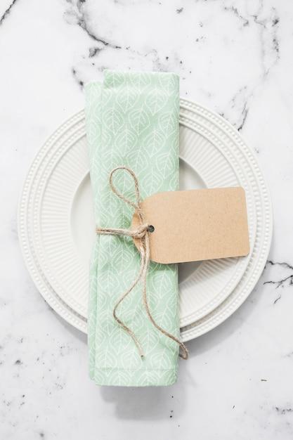 Guardanapo dobrado amarrado com tag em branco em um prato redondo liso vazio Foto gratuita