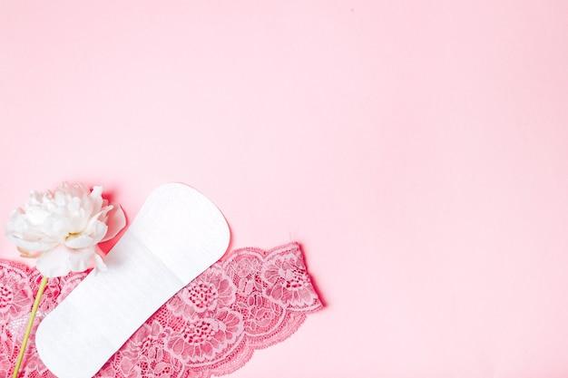 Guardanapo sanitário com uma linda peônia e roupas íntimas em uma superfície rosa Foto Premium