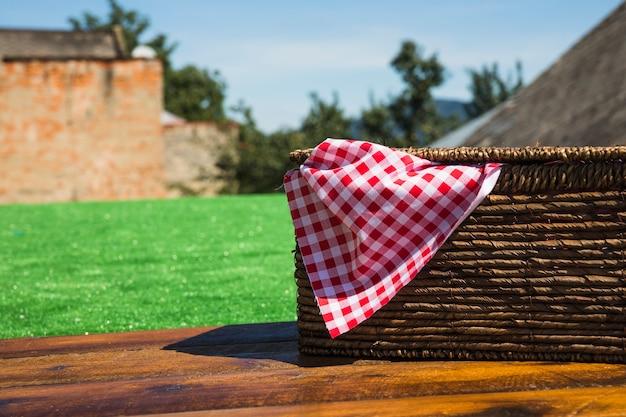 Guardanapo xadrez vermelho dentro da cesta de piquenique na mesa de madeira no exterior Foto gratuita