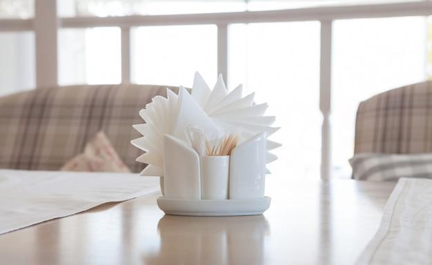 Guardanapos brancos em titulares na mesa de madeira, close-up Foto Premium