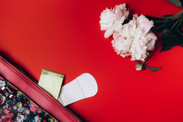 Guardanapos sanitários destacam-se da sacola e no canto estão lindas peônias Foto Premium