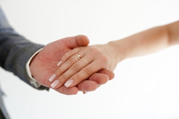 Guardando as mãos com alianças de casamento no branco com espaço da cópia. Foto Premium