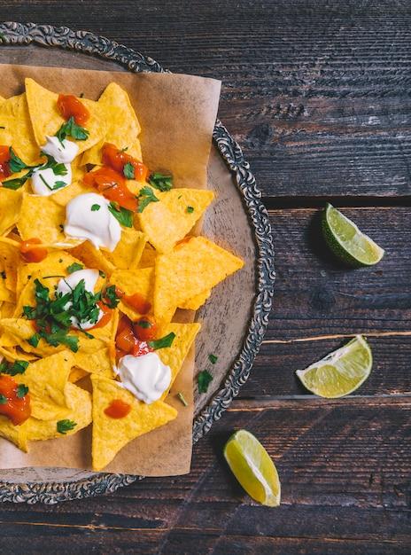 Guarnecido saboroso nachos mexicanos em placa com fatias de limão na mesa de madeira Foto gratuita