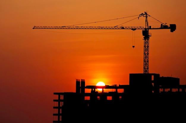 Guindaste de construção no canteiro de obras com ambiente por do sol Foto Premium