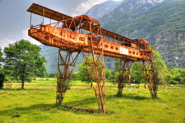 Guindaste de pórtico enferrujado em campo verde com montanhas Foto gratuita