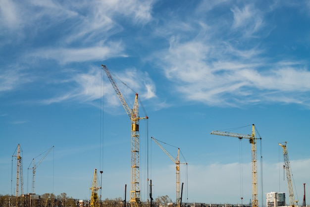 Guindastes de torre grandes acima das construções sob a construção contra o céu azul. Foto Premium