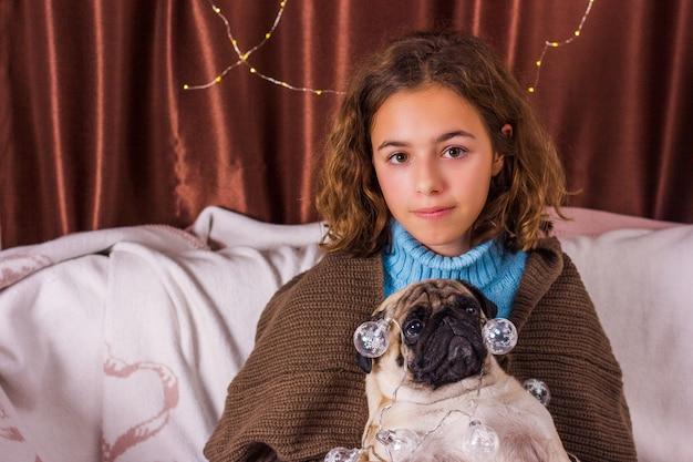 Guirlanda de chistmas no cão pug. menina encantadora com um pug muito engraçado. menina encaracolada abraça um pug Foto Premium