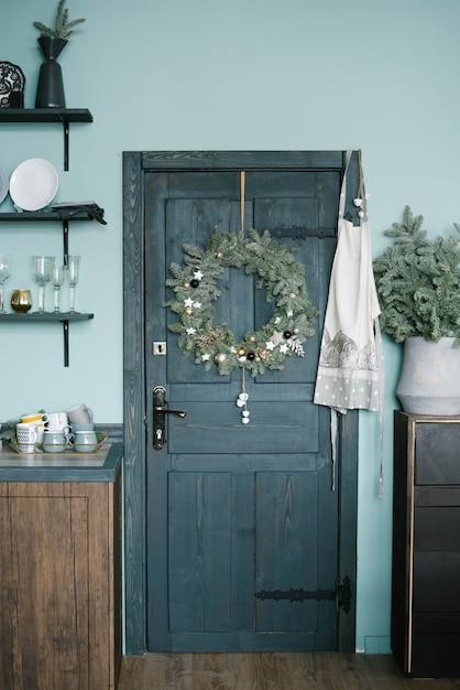 Guirlanda de natal na porta de madeira da cozinha em estilo escandinavo em tons de azul Foto Premium