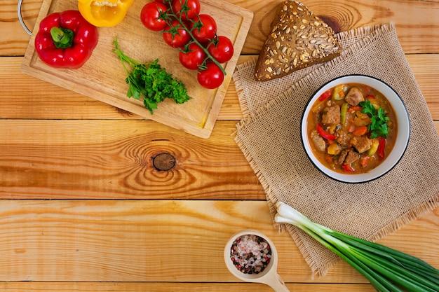 Guisado com carne e legumes em molho de tomate na madeira. vista do topo Foto Premium