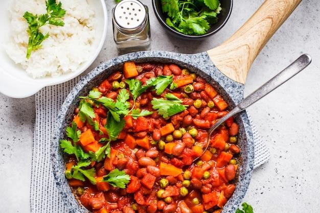 Guisado de feijão vegano com tomate e arroz em uma panela Foto Premium