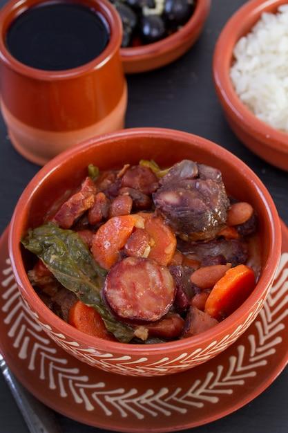 Guisado em tigela de cerâmica com arroz e azeitonas Foto Premium