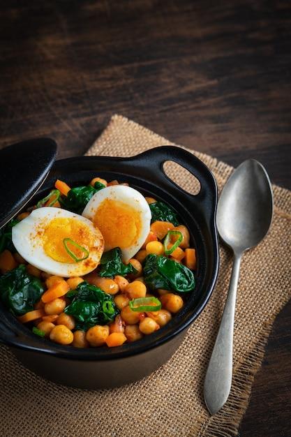 Guisado espanhol do grão-de-bico e dos espinafres com os ovos no fundo de madeira rústico. cozinha espanhola. Foto Premium