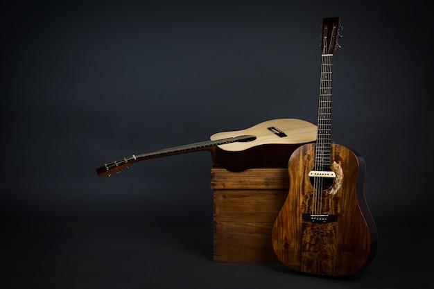 Guitarra acústica em uma cadeira e guitarra marrom close-up na parede preta. Foto gratuita