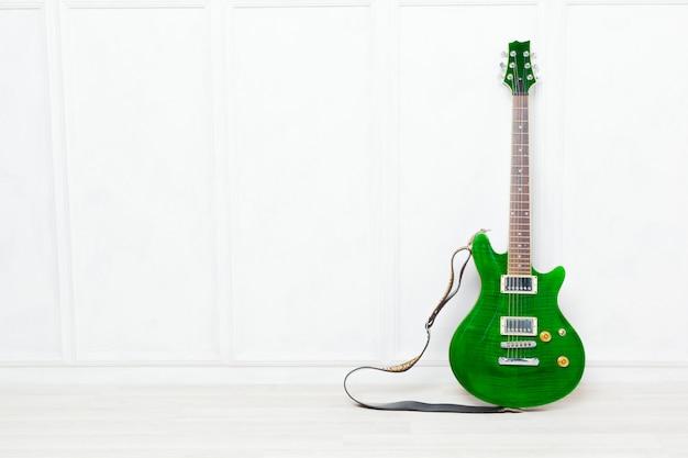 Guitarra apoiada na frente de um fundo de parede branca Foto Premium