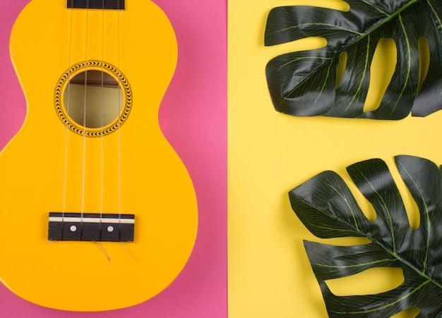 Guitarra de ukulele amarelo brilhante e folhas de monstera Foto Premium