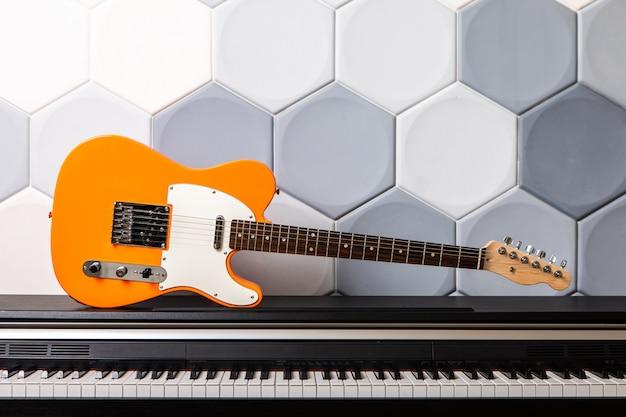 Guitarra elétrica alaranjada que coloca no piano. conceito para escola de música Foto Premium