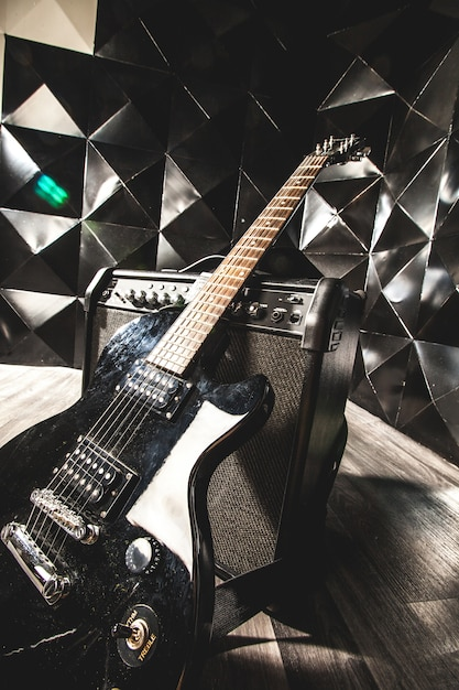 Guitarra elétrica e amplificador clássico em um fundo escuro Foto Premium