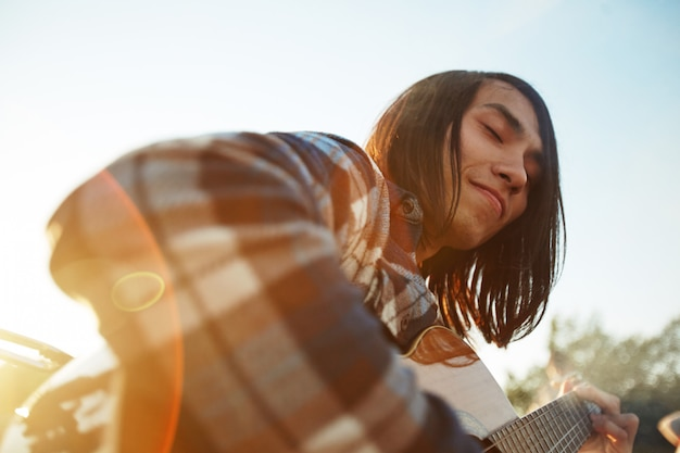 Guitarrista bonito, aproveitando o dia de verão Foto gratuita