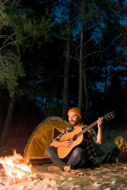 Guitarrista cantando à noite por uma tenda com uma fogueira Foto gratuita