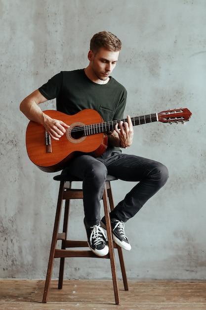 Guitarrista homem tocando violão em casa Foto gratuita