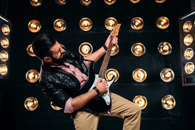 Guitarrista masculino no palco com decorações de luzes Foto Premium