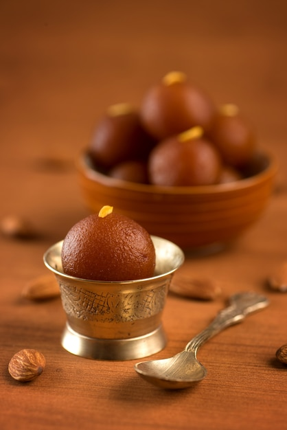 Gulab jamun na tigela e tigela antiga de cobre com colher. sobremesa indiana ou prato doce. Foto Premium