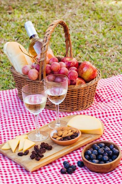 Guloseimas de piquenique de alto ângulo para dois com taças de vinho Foto gratuita