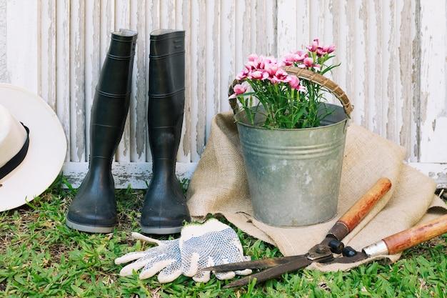 Gumboots com flores e ferramentas no jardim Foto gratuita