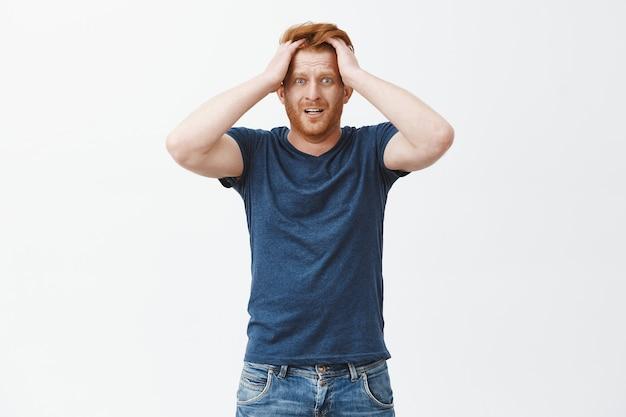 Guy começa a entrar em pânico. nervoso e ansioso homem ruivo atraente com barba, tocando o cabelo, olhando chocado e preocupado Foto gratuita