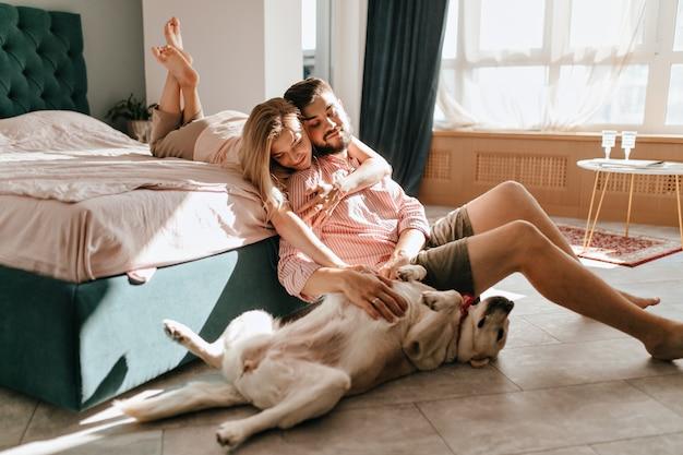 Guy e sua namorada estão descansando no quarto. casal feliz olhando amorosamente para seu animal de estimação que quer brincar. Foto gratuita