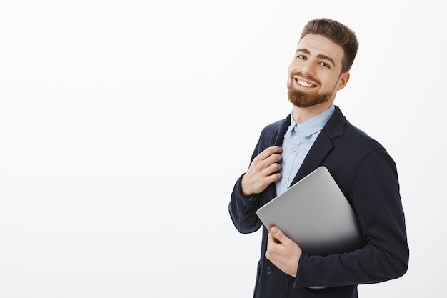 Guy pode lidar com qualquer tarefa sentindo-se autoconfiante e satisfeito, tocando o terno segurando o laptop no braço, de pé meio virado sobre a parede cinza, olhando encantado e satisfeito com o próprio plano de sucesso Foto gratuita