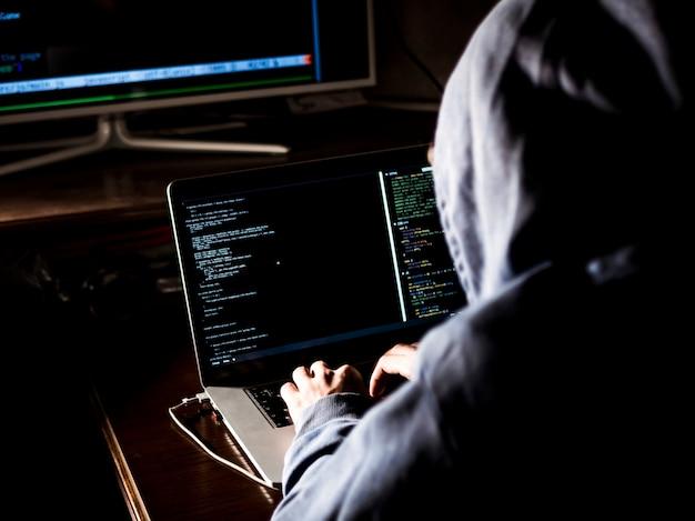 Hacker com capuz digitando código no programa usando o laptop no escuro studio Foto Premium
