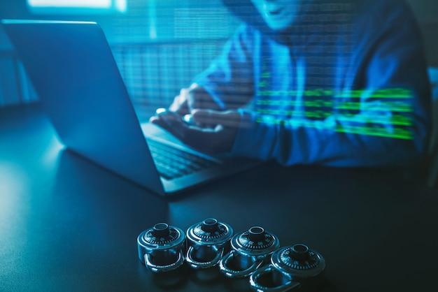 Hacker de povos asiáticos usa uma máscara usando um ataque cibernético de laptop. Foto Premium
