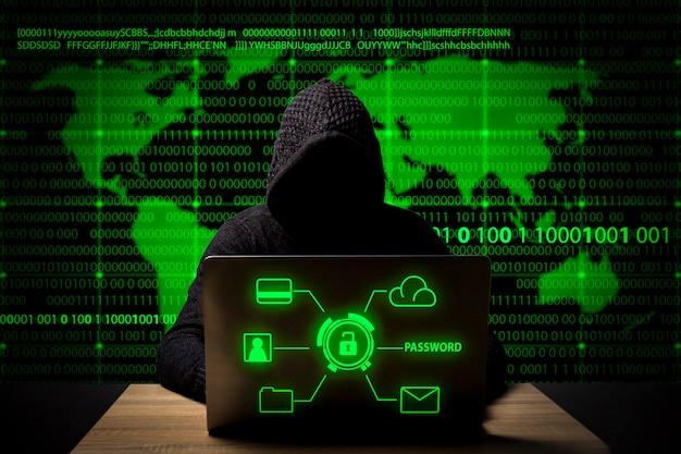 Hacker em uma jaqueta com capuz com um laptop se senta à mesa Foto Premium