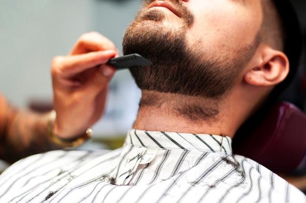 Hairstylist, penteando, barba cliente Foto gratuita