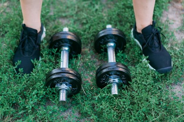 Halteres em fundo de grama verde e foots em tênis pretos Foto gratuita