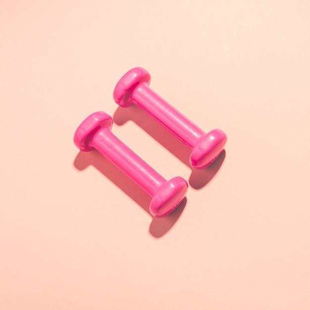 Halteres flat leigos sobre fundo rosa Foto gratuita