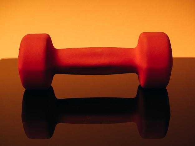 Halteres laranja para fitness em um fundo laranja. refletido a partir da superfície de vidro da balança. conceito de esportes e estilo de vida saudável. Foto Premium