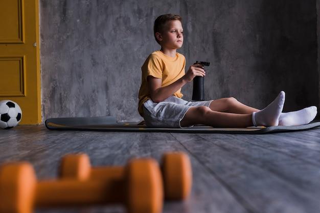Halteres na frente do rapaz sentado no colchonete com garrafa de água Foto gratuita
