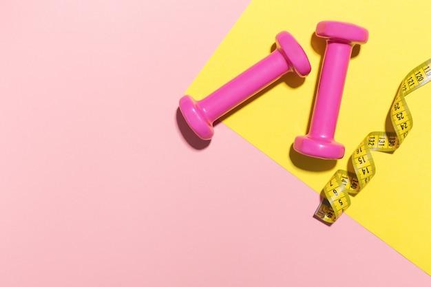 Halteres plana leigos sobre fundo rosa e amarelo Foto gratuita